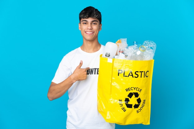 Holding a bag full of plastic bottles to recycle over blue background with surprise facial expression