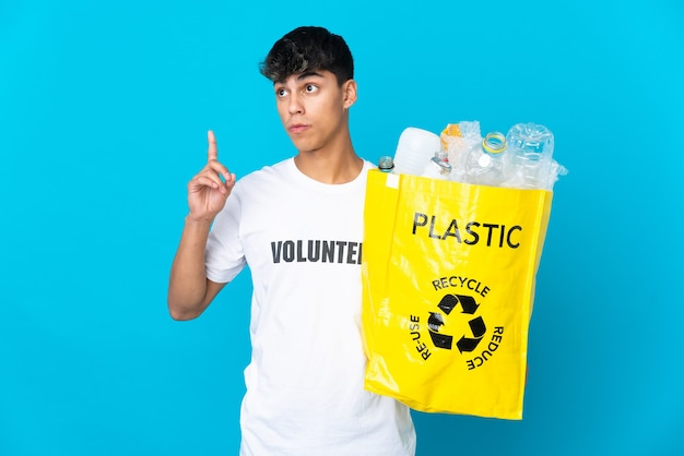 Holding a bag full of plastic bottles to recycle over blue thinking an idea pointing the finger up