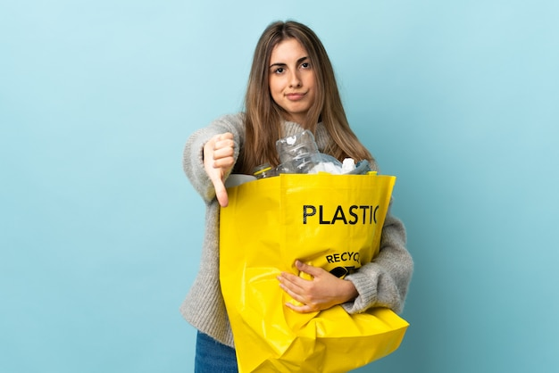 Holding a bag full of plastic bottles to recycle over isolated blue showing thumb down sign