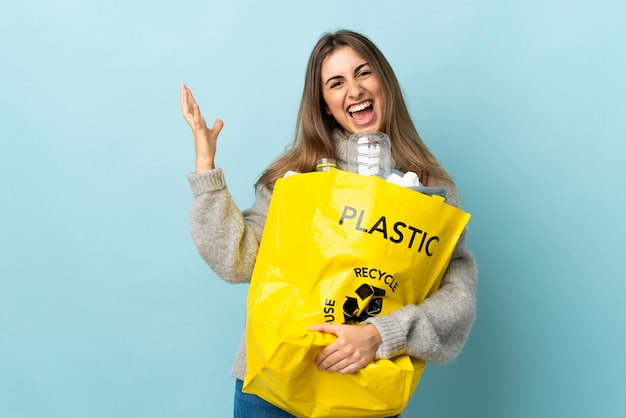 Holding a bag full of plastic bottles to recycle on isolated blue unhappy and frustrated with something