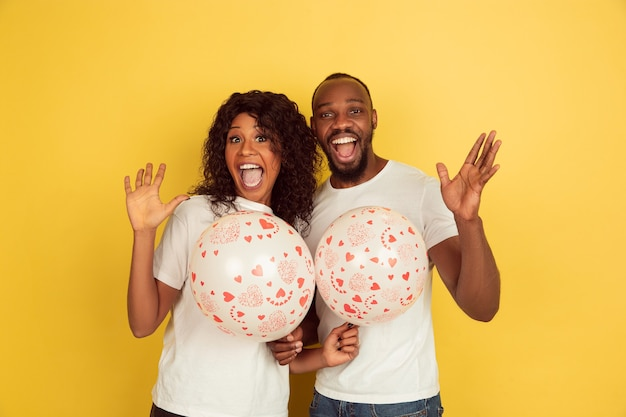 Tenendo palloncini. celebrazione di san valentino, felice coppia afro-americana isolata su sfondo giallo studio. concetto di emozioni umane, espressione facciale, amore, relazioni, vacanze romantiche.