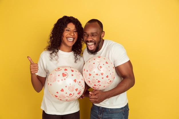 Tenendo palloncini. celebrazione di san valentino, felice coppia afro-americana isolata sulla parete gialla. concetto di emozioni umane, espressione facciale, amore, relazioni, vacanze romantiche.