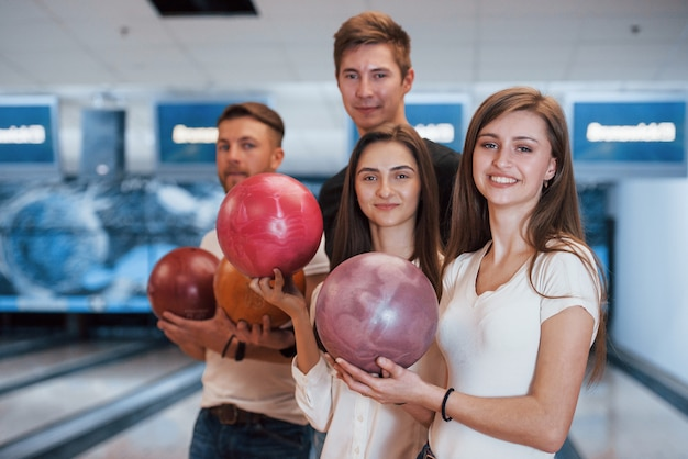Tenendo le palle in mano. i giovani amici allegri si divertono al bowling durante i fine settimana