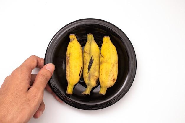 Держит банан на тарелке, изолированной на белом фоне