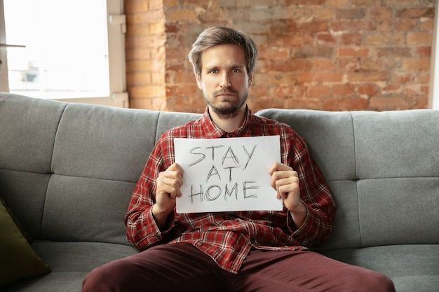 Holding banner stay at home sitting on sofa in room