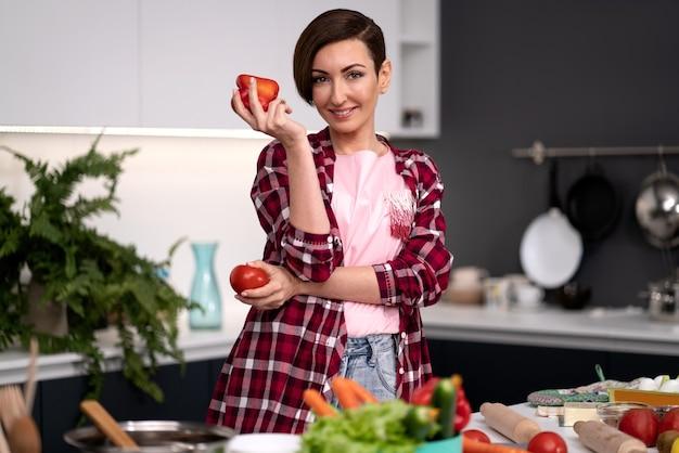ピーマンとトマトを手に、チェック柄のシャツに短い髪型の野菜料理を着た主婦