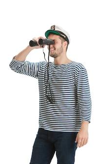 쌍안경을 들고. 흰색 스튜디오 벽에 제복을 입은 백인 남성 선원.