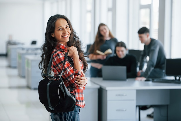 黒い袋を保持しています。近代的なオフィスで働くカジュアルな服装の若い人たちのグループ