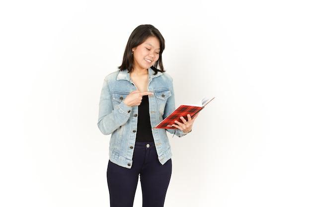 흰색에 고립 된 청바지 재킷과 검은 셔츠를 입고 아름 다운 아시아 여자의 책을 들고