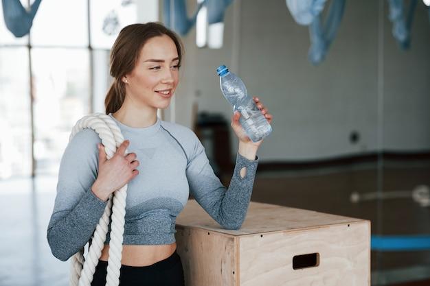Держа бутылку с водой. спортивная молодая женщина имеет фитнес-день в тренажерном зале в утреннее время