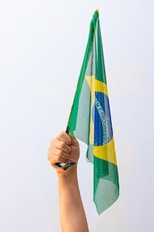 흰색 배경에 고립 된 브라질 국기를 들고. 플래그 및 독립 기념일 개념 이미지입니다.