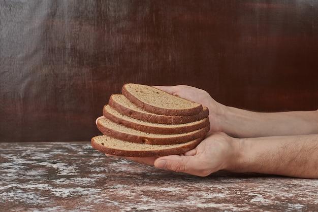 手にパンのスライスを持っています。