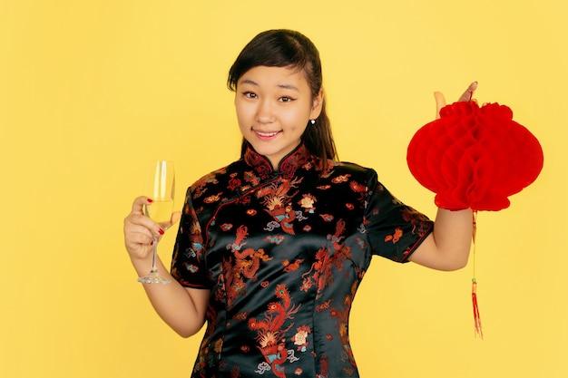 シャンパンとランタンを持っています。ハッピーチャイニーズニューイヤー2020。黄色の背景にアジアの若い女の子の肖像画。伝統的な服を着た女性モデルは幸せそうに見えます。お祝い、感情。コピースペース。