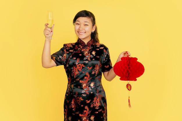샴페인과 랜턴을 들고. 해피 중국 설날. 노란색 바탕에 아시아 젊은 여자의 초상화. 전통 옷을 입은 여성 모델이 행복해 보입니다. copyspace.