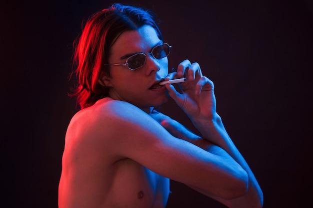 Держит сигарету. студия снята в темной студии с неоновым светом. портрет серьезного мужчины.