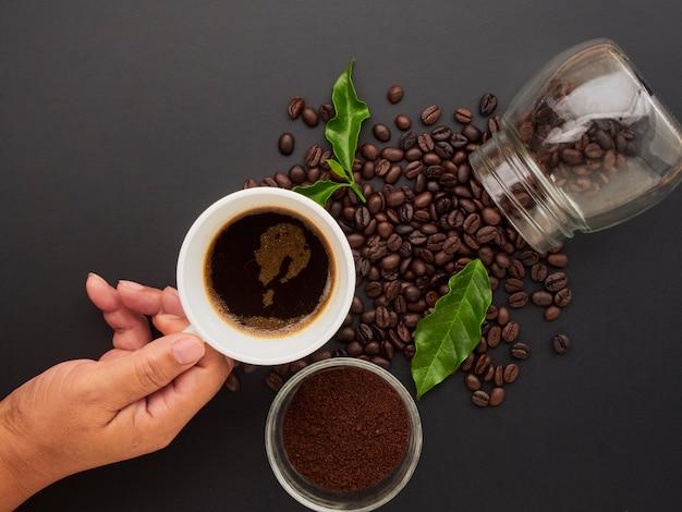 Держа чашку кофе на кофейных зерен.
