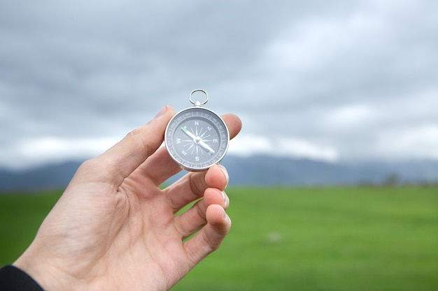 Holding a compass against the scene of a green field during the day