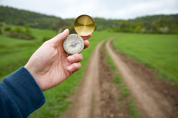 Holding a compass on the scene of a dirt road