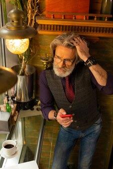 通信を保持します。コーヒーショップのテーブルの近くに立って髪を固定し、メッセージへの応答について考えているハンサムな成人男性。