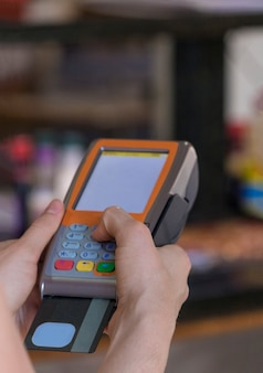 Holding a credit card payment swipe machine in a restaurant