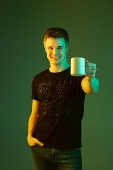 컵을 들고 웃고. 네온 불빛에 녹색 스튜디오 배경에 고립 된 백인 남자의 초상화.