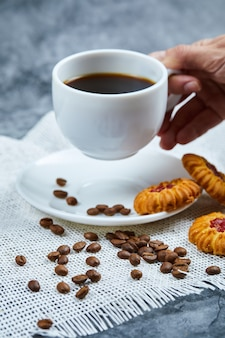 Holding a cup of coffee with biscuits and coffee beans.