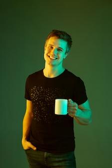 Tenendo la tazza e sorridente. ritratto di uomo caucasico isolato su sfondo verde in luce al neon.