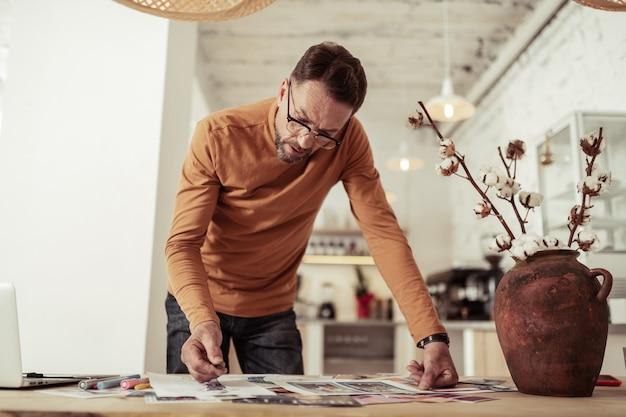 자신과 토론하기. 사려 깊은 패션 디자이너는 그의 작업에 깊이있는 스케치로 테이블을 구부리고 있습니다.