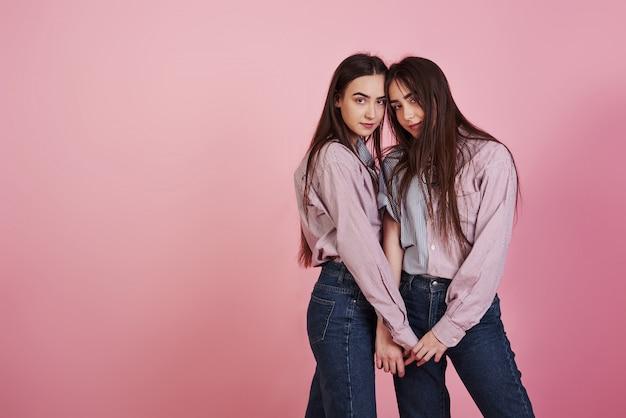 Держа друг друга за руки. молодые женщины с удовольствием. очаровательные близнецы