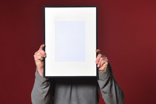 Holding a frame on red background