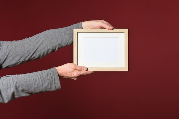 Holding a frame of wood on red background