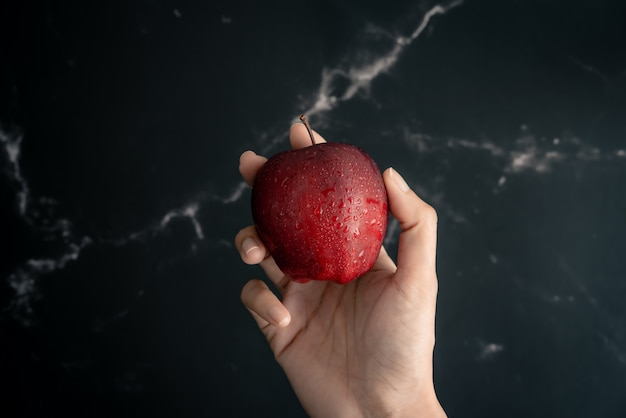 Holding fresh juicy red apple with water spray droplets on apple in hand over a black marble surface. top view flat lay composition.