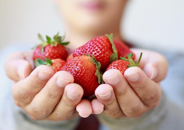 新鮮なイチゴを手に持って