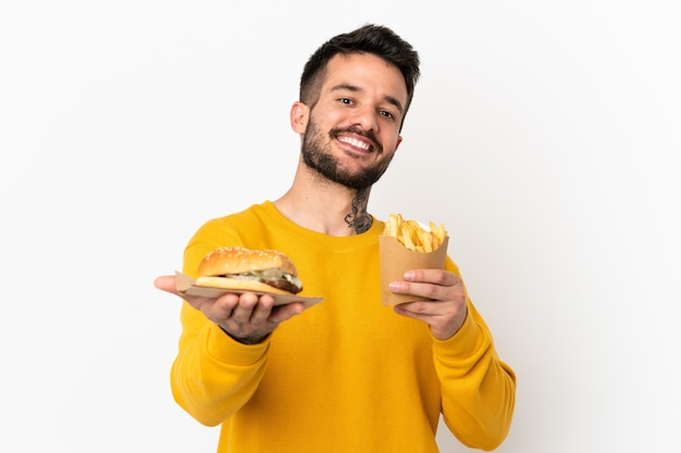 Держа жареные чипсы и чизбургер на изолированном фоне