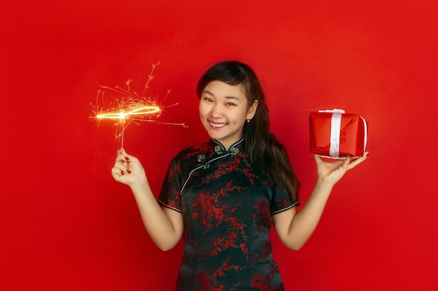 Holding giftbox and bright sparkler. happy chinese new year. asian young girl's portrait on red background. female model in traditional clothes looks happy.  copyspace.