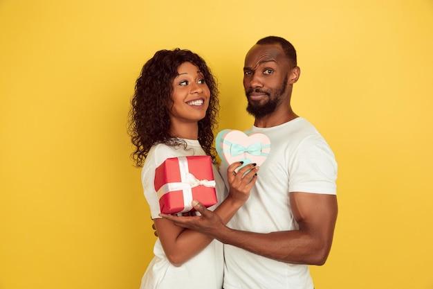 ギフトボックスを持っています。バレンタインデーのお祝い、黄色のスタジオの背景に分離された幸せなアフリカ系アメリカ人のカップル。