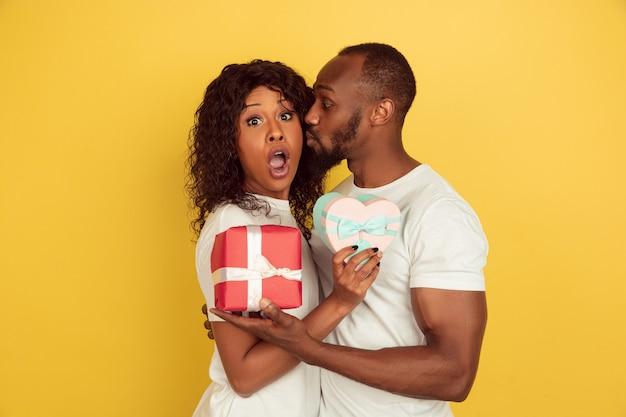 ギフトボックスを持っています。バレンタインデーのお祝い、黄色の壁に隔離された幸せなアフリカ系アメリカ人のカップル。人間の感情、顔の表情、愛、関係、ロマンチックな休日の概念。