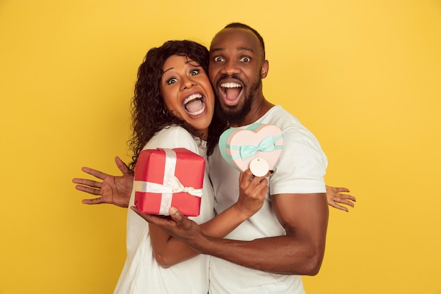 Holding giftboxes. valentine's day celebration, happy african-american couple isolated on yellow studio background.