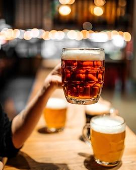 Держа стеклянную кружку темного пива в баре