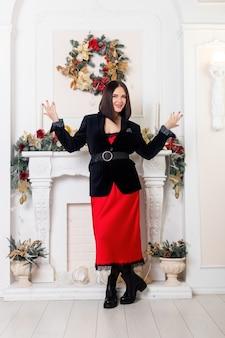 샴페인 잔을 손에 들고 크리스마스 트리 근처에서 포즈를 취합니다. 크리스마스 트리 조명 배경 위에 빨간 치마와 검은 재킷에 우아한 아가씨. 새해 복 많이 받으세요.