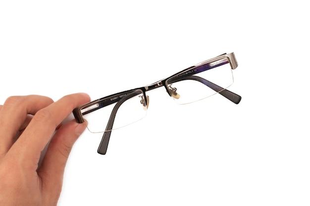 白い背景にメガネを保持します。