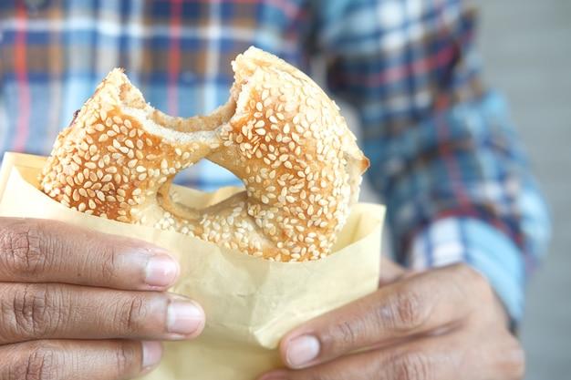 종이에 반 먹은 신선한 베이글 빵을 들고
