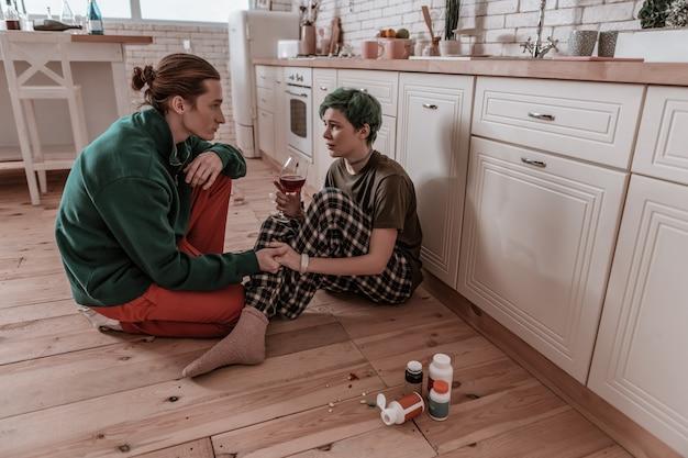 Держась за руку. любящий муж держит за руку свою жену, сидящую на полу и испытывающую проблемы с алкоголем