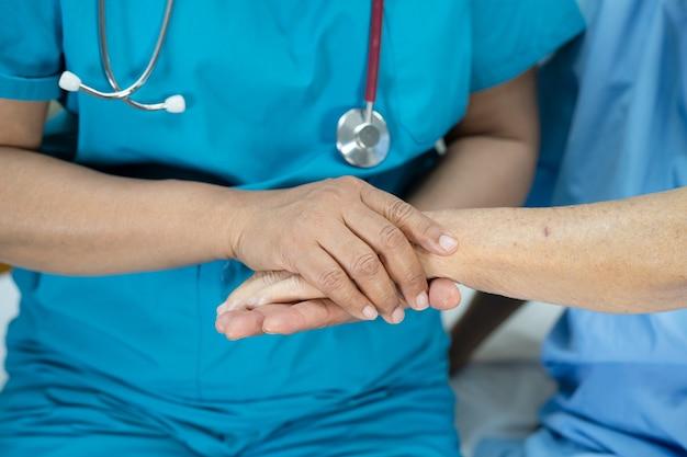 手をつないで看護で愛、ケア、励ましと共感を持つアジアのシニアまたは高齢の老婦人女性患者