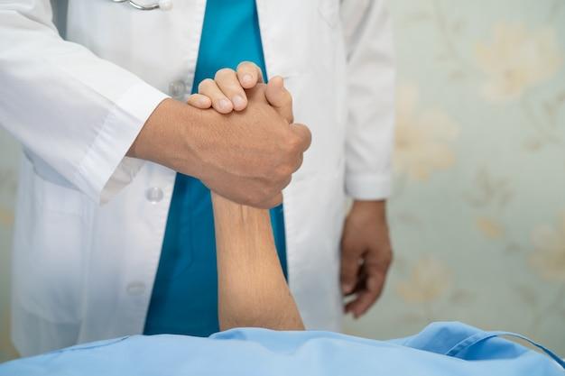手をつないで愛のケアと共感を持つアジアの年配の女性患者