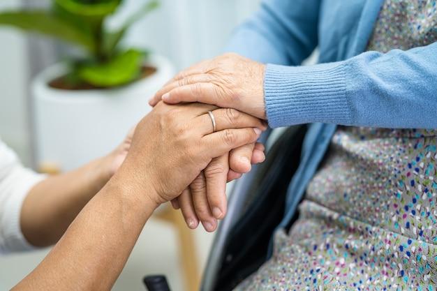 愛を持って手をつないでアジアの年配の女性患者