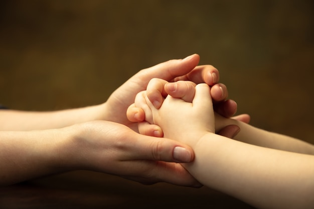 Holding hands, clapping like friends. close up shot of female and kid's hands doing different things together. family, home, education, childhood, charity concept. mother and son or daughter, wealth.