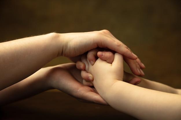 손을 잡고 친구처럼 박수 친다. 함께 다른 일을하는 여성과 아이의 손의 총을 닫습니다. 가족, 가정, 교육, 어린 시절, 자선 개념. 어머니와 아들 또는 딸, 부.
