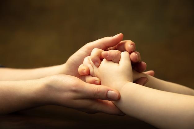 Держась за руки, хлопая как друзья. крупным планом женские и детские руки делают разные вещи вместе. семья, дом, образование, детство, концепция благотворительности. мать и сын или дочь, богатство.