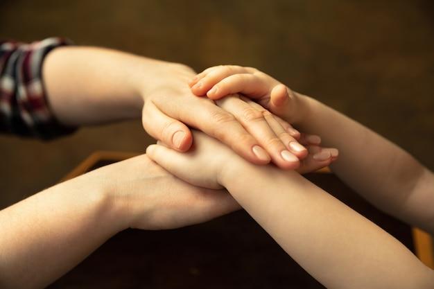 手をつないで、あたたかい気持ち。さまざまなことを一緒にやっている女性と子供の手の接写。家族、家、教育、子供時代、チャリティーのコンセプト。母と息子または娘、富。